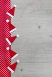 Weihnachtshut-, Rotes und weißestupfengewebe auf grauem hölzernem Ba Stockfotografie