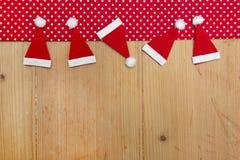 Weihnachtshut-, Rotes und weißestupfengewebe auf hölzernem backgro Stockfotos