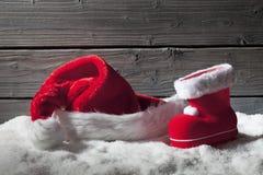 Weihnachtshut und -stiefel auf Haufen des Schnees gegen hölzernen Hintergrund Lizenzfreies Stockbild