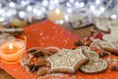 Weihnachtsingwerplätzchen, -kerze, -mandeln und -gewürze auf einem roten und hölzernen Hintergrund Lizenzfreies Stockfoto