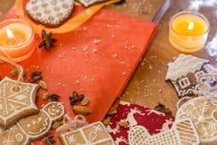 Weihnachtsingwerplätzchen, -kerzen, -mandeln und -gewürze auf einem roten Papier und einem Holz Stockfotografie