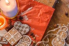 Weihnachtsingwerplätzchen, -kerzen und -gewürze auf einem roten und hölzernen Hintergrund Stockbilder