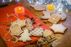 Weihnachtsingwerplätzchen mit weißer Zuckerglasur auf einem roten und braunen Hintergrund Stockbild