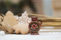Weihnachtsinnenraum mit einem kleinen keramischen Krug und gingerbreadgs stockfotos