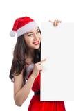 Weihnachtsjunge asiatische Frau, die leeres Anschlagtafelfahnenzeichen zeigt Lizenzfreie Stockbilder