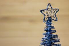 Weihnachtskünstlicher kleiner blauer Weihnachtsbaum auf einem braunen Hintergrund Stockfoto