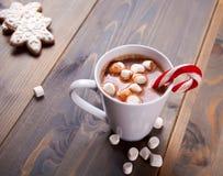 Weihnachtskakao mit Eibischen, Zuckerstange und Plätzchen auf dem Holztisch stockfoto