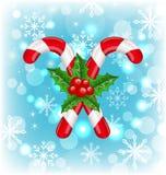 Weihnachtskaramelstöcke mit Stechpalmenbeere, glühender Hintergrund Stockfotos