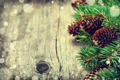 Weihnachtskarte des Tannenbaums und des Nadelbaumkegels auf rustikalem hölzernem Hintergrund Lizenzfreies Stockbild