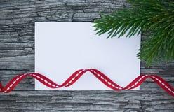 Weihnachtskarte: leere Papierform mit Tannenbaum verzweigt sich auf hölzernen Hintergrund Stockfotos