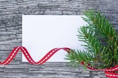 Weihnachtskarte: leeres Papier mit Tannenbaum verzweigt sich auf hölzernen Hintergrund Lizenzfreies Stockbild