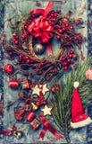 Weihnachtskarte mit Dekoration, Winterbeere Kranz-, Sankt-Hut und Plätzchen auf rustikalem hölzernem Hintergrund Lizenzfreie Stockfotos
