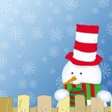 Weihnachtskarte mit dem Schneemann, der über dem Zaun schaut Lizenzfreies Stockfoto