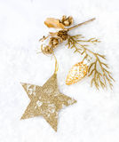 Weihnachtskarte mit goldenem Stern und Dekorationen auf Schnee   Lichter Stockfotografie