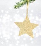 Weihnachtskarte mit goldenem Stern und Kiefer verzweigen sich auf Defocused Chr Stockbild