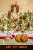 Weihnachtskarte mit Keksen auf rotem Band- und Spitzerand, Schokoladenherzen mit einem Bogen und Zweigen von Thuja Stockbild