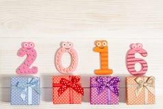 Weihnachtskarte mit lustigen Nr. 2016 und Geschenkboxen Stockfotografie