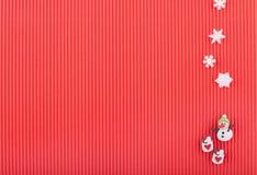 Weihnachtskarte mit Schneemann, zwei Schalen mit Herzen und Schneeflocken auf roter Wellpappe Stockbilder
