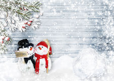Weihnachtskarte mit Schneemännern, Stechpalme und Tannenzweigen auf Holz Lizenzfreies Stockbild