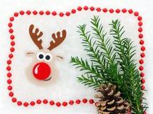 Weihnachtskarte rot und weiß, Ren, christmastree, Kiefernkegel, Girlande im Schnee Stockfotografie