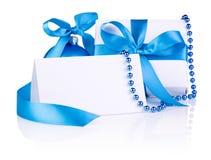 Weihnachtskarte und -geschenk mit blauer Kugel, Farbbandbogen Stockfoto