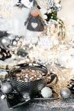 Weihnachtskarten-Luxusweihnachten, silberne Schale süße Creme auf grauer Tabelle, mit Bonbons, Zimt, Anissamen, Winterkegel und l stockbild