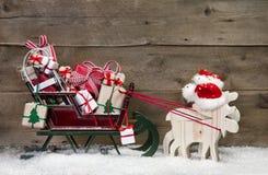 Weihnachtskartendekoration: Elche, die Sankt-Pferdeschlitten mit Geschenken ziehen Lizenzfreies Stockbild
