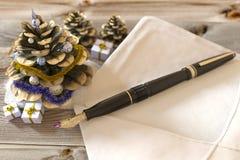 Weihnachtskegel mit Geschenken, Stift und Buchstaben Stockfotografie