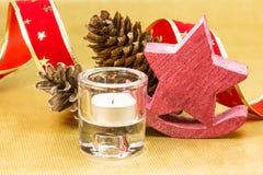 Weihnachtskerze mit Dekoration über goldenem Hintergrund Lizenzfreies Stockfoto