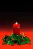 Weihnachtskerze mit Stechpalme und Efeu auf rotem Hintergrund. Stockfoto