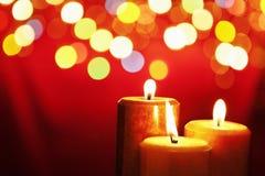 Weihnachtskerze mit unscharfer Leuchte Stockfotografie