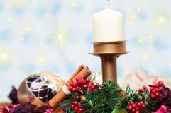 Weihnachtskerze mit Zimt und Kugeln Stockfoto