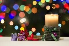 Weihnachtskerze und Geschenk-Dekorationen auf Blured-Feiertags-Hintergrund Stockfotos