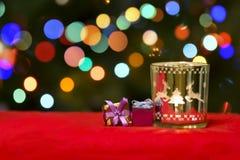 Weihnachtskerze und Geschenk-Dekorationen auf Blured-Feiertags-Hintergrund Lizenzfreies Stockfoto