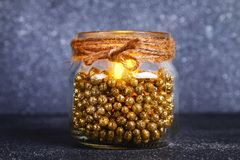 Weihnachtskerze von einem Glas - wie man einen schönen Kerzenständer mit einer elektrischen Kerze herstellt, die von den Schrottm stockfotografie