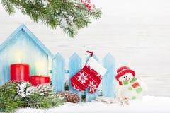 Weihnachtskerzen, Schneemannspielzeug und Tannenbaum stockfotografie