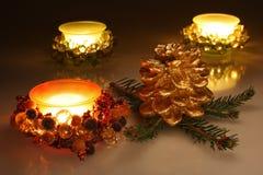 Weihnachtskerzen und goldener Kieferkegel Stockfotos