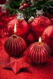 Weihnachtskerzen und -kugeln im Rot Stockbilder