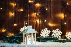 Weihnachtskerzenlaterne und Weihnachtsbaumaste, Schnee, Schneeflocke und Dekorationen auf bokeh Hintergrund verwischten Lichter Lizenzfreies Stockbild