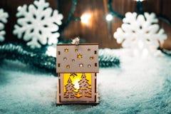 Weihnachtskerzenlaterne und Weihnachtsbaumaste, Schnee, Schneeflocke und Dekorationen auf bokeh Hintergrund verwischten Lichter Stockbild