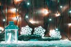 Weihnachtskerzenlaterne und Weihnachtsbaumaste, Schnee, Schneeflocke und Dekorationen auf bokeh Hintergrund verwischten Lichter Stockfoto