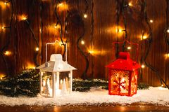 Weihnachtskerzenlaterne und Weihnachtsbaumaste, Schnee, Schneeflocke und Dekorationen auf bokeh Hintergrund verwischten lig Stockfotografie