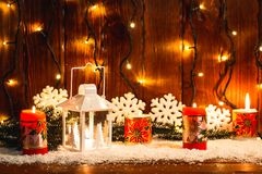 Weihnachtskerzenlaterne und Weihnachtsbaumaste, Schnee, Schneeflocke und Dekorationen auf bokeh Hintergrund verwischten lig Stockfoto