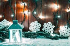 Weihnachtskerzenlaterne und Weihnachtsbaumaste, Schnee, Schneeflocke und Dekorationen auf bokeh Hintergrund verwischten lig Lizenzfreie Stockbilder