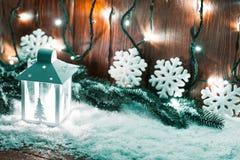 Weihnachtskerzenlaterne und Weihnachtsbaumaste, Schnee, Schneeflocke und Dekorationen auf bokeh Hintergrund verwischten lig Stockbild
