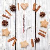 Weihnachtskiefernkegel-Uhrdekoration auf weißem hölzernem Brett Stockfotos