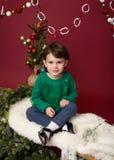 Weihnachtskind auf Schlitten gegen Weihnachtsbaum mit Verzierungen Lizenzfreie Stockbilder