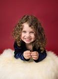 Weihnachtskind: Glückliches Mädchen auf rotem Hintergrund Lizenzfreies Stockfoto