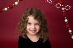 Weihnachtskind: Glückliches Mädchen auf rotem Hintergrund Stockfotografie