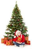 Weihnachtskind in Sankt-Hut, Geschenkbox unter Tannenbaum Lizenzfreies Stockbild
